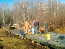 Manpower from two clubs complete a 300-foot bridge east of Minong WI, October 2009. The bridge allows ATV's to use a snowmobile trail that crosses a wetland. The deck is wavy, because you can't do any digging or filling in a wetland to level it out. If you are wondering why a bridge is being built across what looks like a grassy field, see previous picture.
