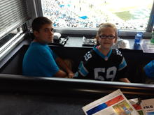 Colby (nephew) and Loralei sitting in box seats at a Panthers football game