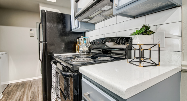 Model kitchen with gray cabinets and gas stove