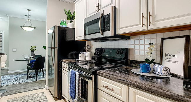 Newly renovated kitchens featuring black-fusion counter tops, white cabinetry, and wood-style flooring.